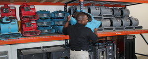 Water Damage Restoration Technician Mobilizing Air Movers For Mold Job